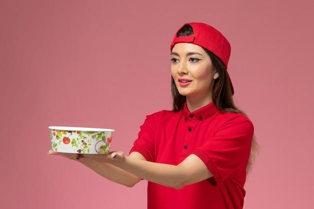 밝은 분홍색 벽, 서비스 배달 직원 작업 소녀에 그녀의 손에 배달 그릇과 빨간색 유니폼 케이프에서 전면보기 여성 택배