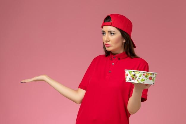 밝은 분홍색 벽, 서비스 소녀 배달 직원에 그녀의 손에 배달 그릇과 빨간 유니폼 케이프에 전면보기 여성 택배