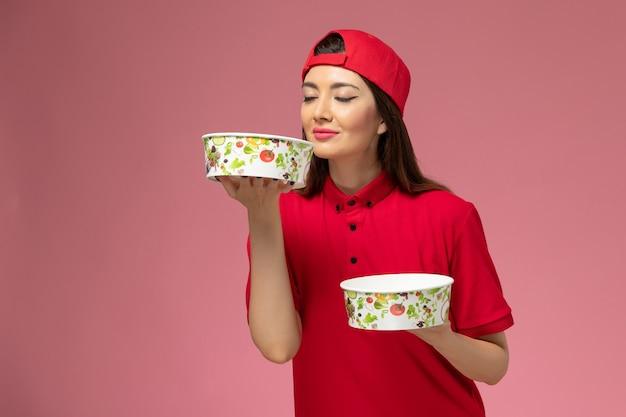 淡いピンクの壁に臭いがする彼女の手に配達ボウルを備えた赤い制服ケープの正面図女性宅配便、サービス配達従業員