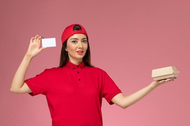 淡いピンクの壁に小さな配達食品パッケージとカードを手にした赤い制服ケープの正面図の女性宅配便、サービス配達従業員の仕事