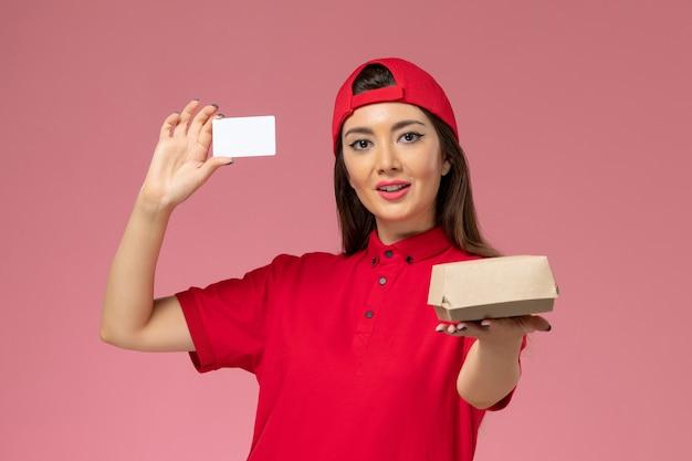 淡いピンクの壁に彼女の手に小さな配達食品パッケージとカード、サービス作業配達従業員と赤い制服ケープの正面図女性宅配便