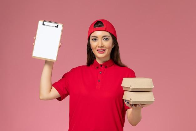 淡いピンクの壁に小さな配達食品パッケージとメモ帳が付いた赤い制服のケープの正面図の女性宅配便、ジョブサービス配達従業員