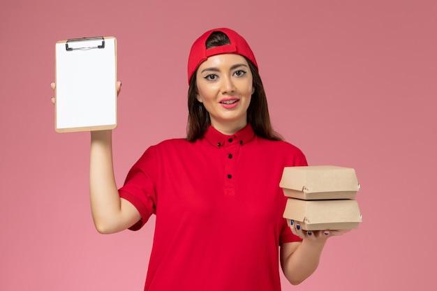 淡いピンクの壁に小さな配達食品パッケージとメモ帳が付いた赤い制服のケープの正面図の女性宅配便、サービス配達の従業員の仕事