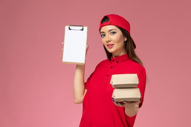 淡いピンクの壁に小さな配達食品パッケージとメモ帳が付いた赤い制服のケープの正面図の女性宅配便、サービス配達の従業員