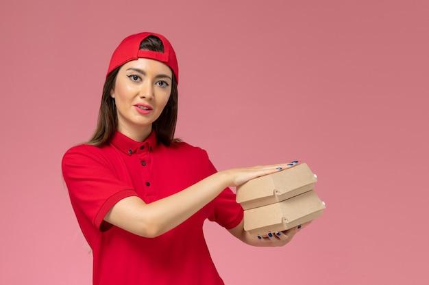 淡いピンクの壁に彼女の手に小さな配達食品パッケージ、サービス提供従業員の仕事と赤い制服ケープの正面図女性宅配便
