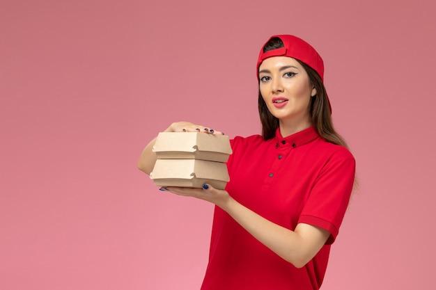 淡いピンクの壁に彼女の手に小さな配達食品パッケージ、サービス提供の従業員と赤い制服ケープの正面図女性宅配便