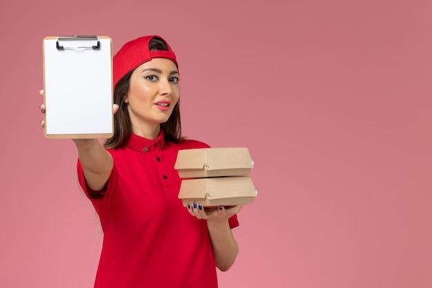 明るいピンクの壁にメモ帳と小さな配達食品パッケージを手にした赤い制服のケープの正面図の女性宅配便、ジョブサービス配達従業員