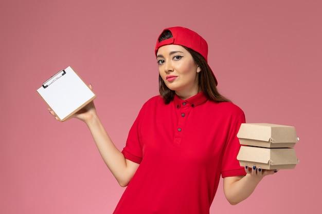 淡いピンクの壁にメモ帳と小さな配達食品パッケージを手にした赤い制服のケープの正面図の女性の宅配便、サービス提供の従業員の仕事