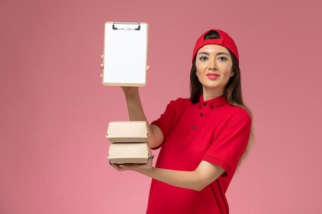 淡いピンクの壁にメモ帳と小さな配達食品パッケージを手にした赤い制服のケープの正面図の女性宅配便、サービス配達従業員労働者の仕事