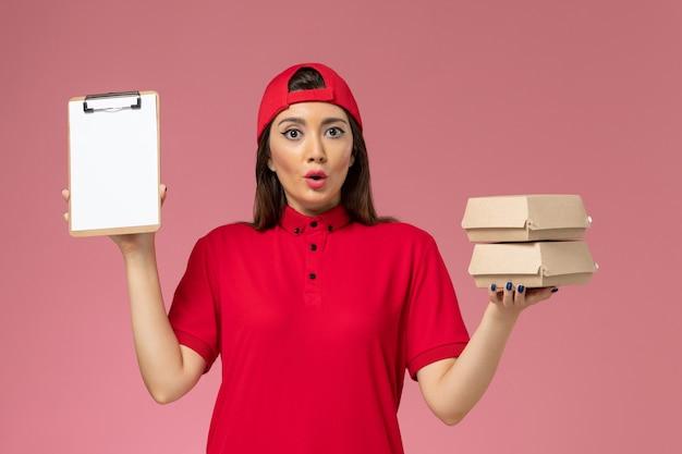 明るいピンクの壁にメモ帳と小さな配達食品パッケージを手にした赤い制服のケープの正面図の女性宅配便、サービス配達従業員