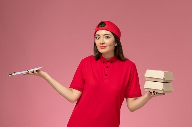 淡いピンクの壁にメモ帳と小さな配達食品パッケージを手にした赤い制服のケープの正面図の女性宅配便、サービス提供の仕事の従業員