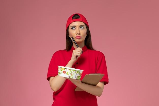 彼女の手に丸い配達ボウルのメモ帳が薄いピンクの壁にメモを書いている赤い制服のケープの正面図の女性の宅配便、制服配達従業員労働者