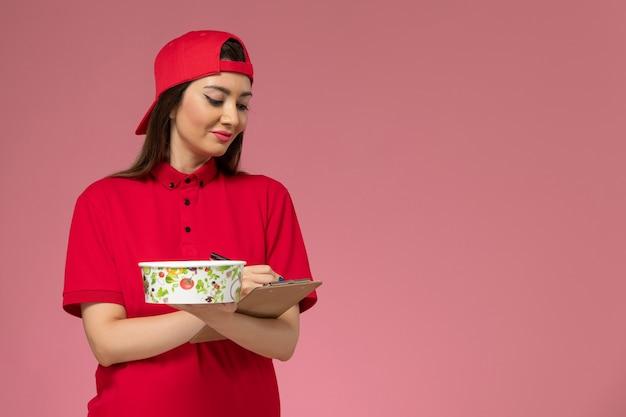 彼女の手に丸い配達ボウルのメモ帳が付いた赤い制服のケープの正面図の女性の宅配便は、淡いピンクの壁にメモを書いています、制服配達の従業員