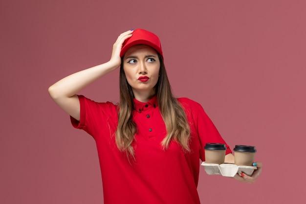 Вид спереди женщина-курьер в красной форме, держащая коричневые кофейные чашки с доставкой и размышляющая на светло-розовом фоне, униформа службы доставки, рабочая работа, женская компания