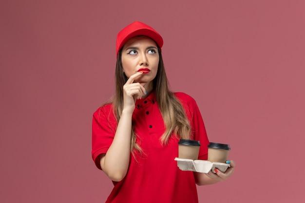 Вид спереди женщина-курьер в красной форме, держащая коричневые кофейные чашки с доставкой и думая на розовом фоне, форма доставки службы, рабочая работа, женская компания