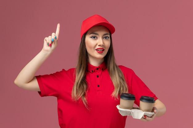 분홍색 배경 서비스 배달 유니폼 작업에 갈색 배달 커피 컵을 들고 빨간 제복을 입은 전면보기 여성 택배