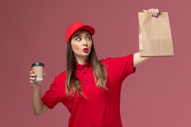 ピンクの背景のサービス配達労働者の制服の仕事で配達コーヒーカップと食品パッケージを保持している赤い制服の正面図女性宅配便