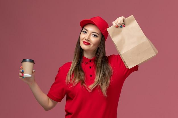 ピンクの背景に笑顔の配達コーヒーカップと食品パッケージを保持している赤い制服の正面図女性宅配便