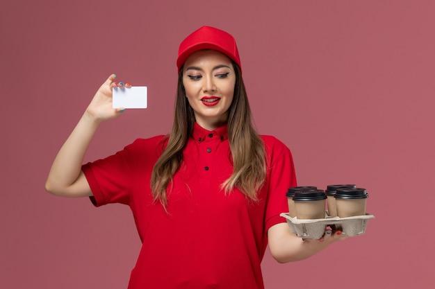 Вид спереди женщина-курьер в красной форме с доставкой кофейных чашек и пластиковой карты на розовом фоне