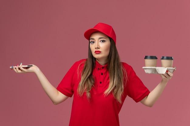 Вид спереди женщина-курьер в красной форме, держащая доставку кофейных чашек и смартфон на светло-розовом фоне, рабочая форма службы доставки
