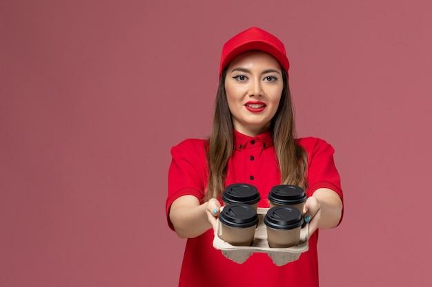 Вид спереди женщина-курьер в красной форме, держащая кофейные чашки и смартфон на розовом столе, униформа службы доставки