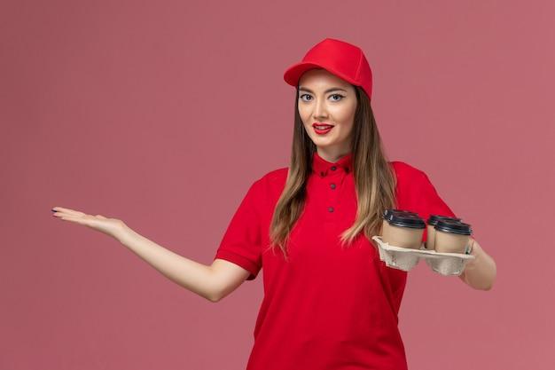 Вид спереди женщина-курьер в красной форме, держащая кофейные чашки и смартфон на розовом столе, рабочая форма службы доставки