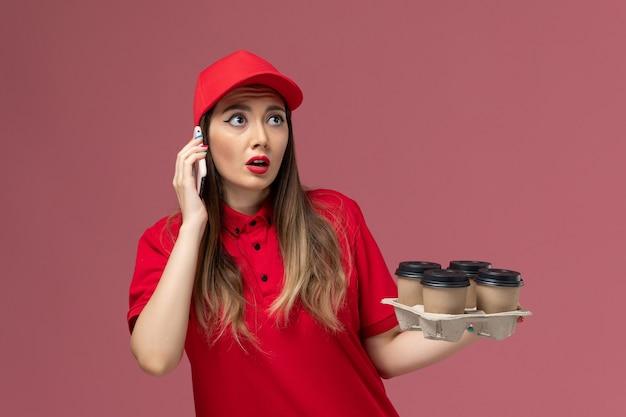 配達コーヒーカップを保持し、ピンクのデスクサービス配達制服で電話で話している赤い制服の正面図女性宅配便
