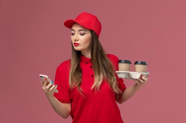 配達コーヒーカップを保持し、ピンクの背景サービス配達制服で彼女の電話を使用して赤い制服を着た女性の宅配便の正面図