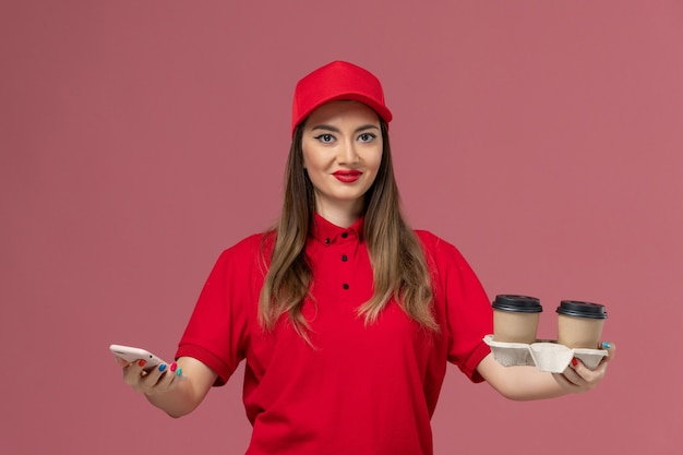 配達コーヒーカップを保持し、ピンクの背景に笑顔の電話を使用して赤い制服を着た女性の宅配便の正面図