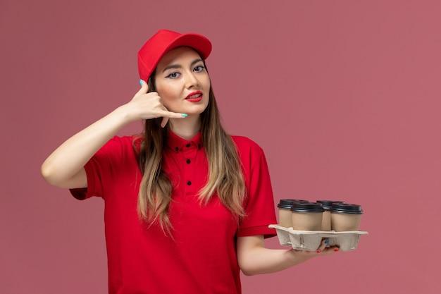 Вид спереди женщина-курьер в красной форме, держащая доставку кофейных чашек на розовом фоне, служба доставки, рабочая форма