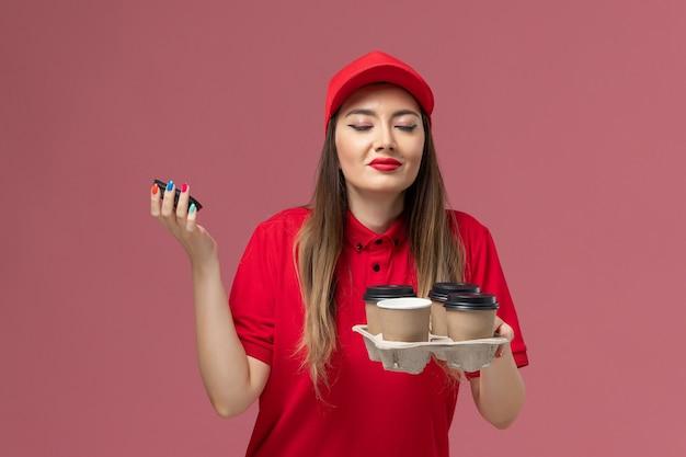 ピンクの背景に香りを嗅ぐ配達コーヒーカップを保持している赤い制服の正面図女性宅配便労働者の仕事サービス配達制服