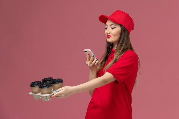분홍색 배경 서비스 배달 회사 작업 유니폼에 그들의 사진을 복용 배달 커피 컵을 들고 빨간 제복을 입은 전면보기 여성 택배