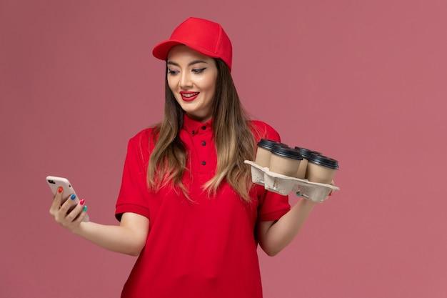 ピンクの背景に彼女の電話を使用して配達コーヒーカップを保持している赤い制服の正面図女性宅配便