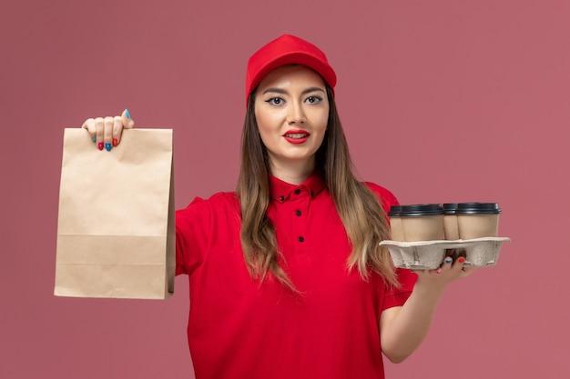 ピンクの背景に食品パッケージと配達コーヒーカップを保持している赤い制服の正面図女性宅配便