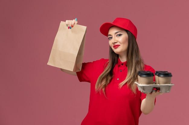 ピンクの背景のサービス配信ユニフォームに食品パッケージと配信コーヒーカップを保持している赤い制服の正面図女性宅配便