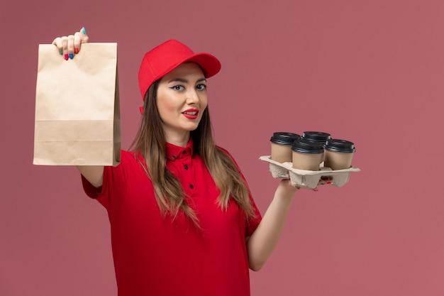 ピンクの背景のサービス配信ジョブユニフォームにわずかな笑顔で食品パッケージと配信コーヒーカップを保持している赤い制服の正面図女性宅配便
