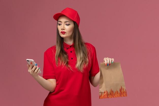 ピンクの背景に電話と食品パッケージを保持している赤い制服を着た正面図の女性の宅配便サービス提供制服の労働者