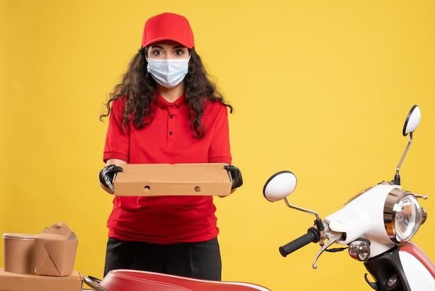 黄色の背景にピザの箱が付いた赤い制服を着た正面の女性宅配便業者が、covid-パンデミックサービスウイルスの仕事を配達する