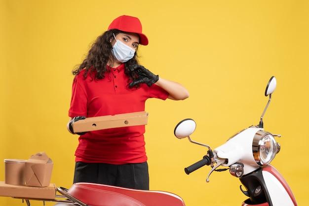 黄色の背景にピザの箱が付いた赤い制服を着た正面の女性宅配便サービスワーカー covid-パンデミックウイルスの仕事