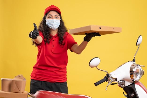 黄色いデスク サービス ワーカー covid- パンデミック ウイルスの仕事の配達にピザの箱が付いている赤い制服を着た正面の女性宅配便