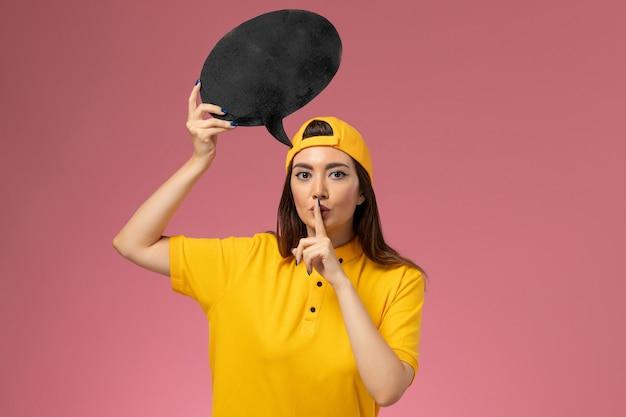 Курьер-женщина в желтой форме и плаще, вид спереди, держит большой черный знак и просит молчать на розовой стене, доставка служебной формы