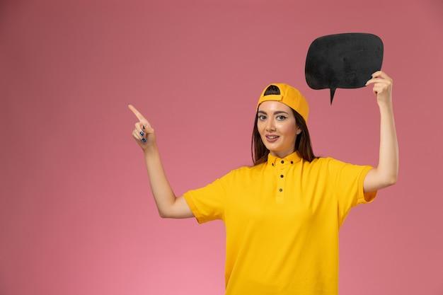 ピンクの壁の作業サービスの制服の配達に大きな黒い看板を保持している黄色の制服と岬の正面図の女性の宅配便