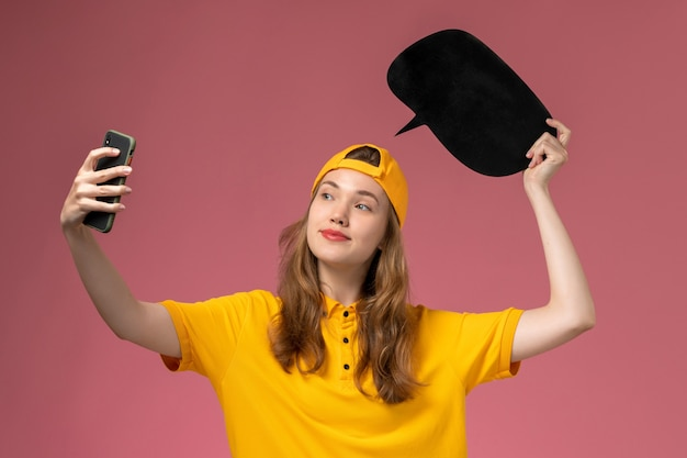 黄色の制服と黒い看板を保持し、ピンクの壁の会社のサービスワーカーの配達制服で写真を撮る岬の正面図の女性の宅配便