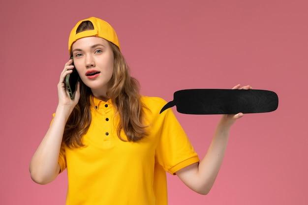 黄色の制服と黒い看板を保持し、ピンクの壁の制服会社のサービス提供の仕事で電話で話している岬の正面図の女性の宅配便