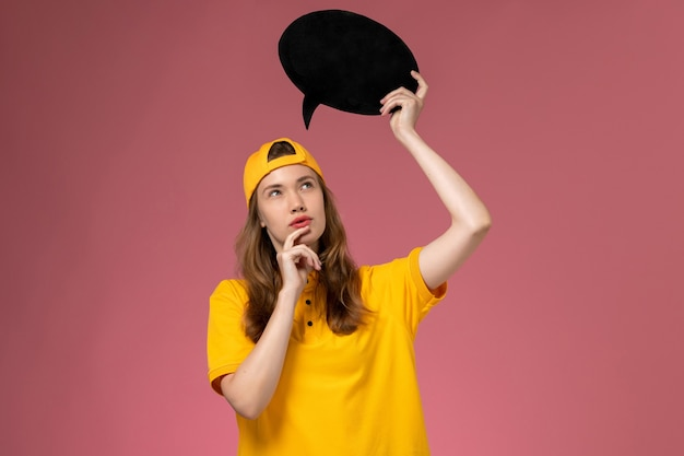 黄色の制服と黒い看板を保持し、ピンクの壁のサービス提供制服を考えている岬の正面図の女性の宅配便