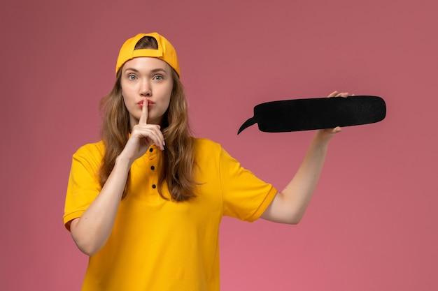 黄色の制服と淡いピンクの壁に黒い看板を保持している岬の正面図の女性の宅配便会社のサービス提供