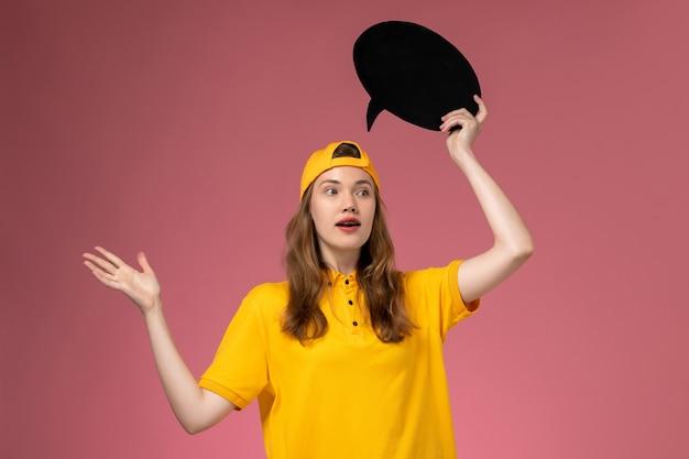 ピンクの壁の会社の仕事の配達の制服の仕事に黒い看板を保持している黄色の制服と岬の正面図の女性の宅配便