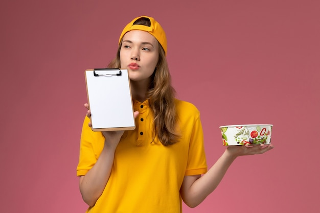 Вид спереди женщина-курьер в желтой униформе и накидке, держащая миску для доставки и блокнот, думающая о светло-розовой стене, униформа службы доставки, работа компании