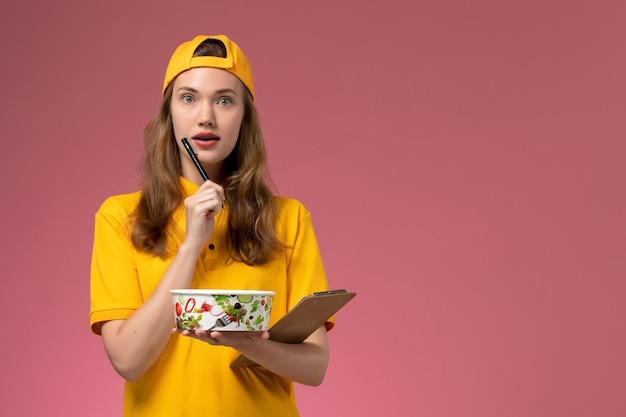 Вид спереди женщина-курьер в желтой форме и накидке держит миску для доставки и блокнот, думая о светло-розовой стене, униформа службы доставки сотрудника службы доставки