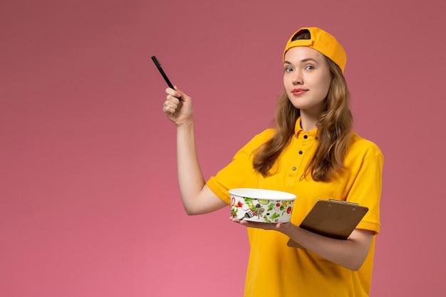 Вид спереди женщина-курьер в желтой униформе и накидке с миской для доставки и блокнотом с ручкой на светло-розовой стене.